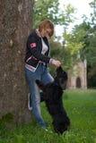 Addestramento della ragazza il suo cane Immagine Stock