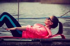 Addestramento della ragazza in vestiti sportivi sulla riva del lago Immagini Stock Libere da Diritti