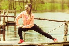 Addestramento della ragazza in vestiti sportivi sulla riva del lago Immagini Stock