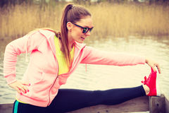 Addestramento della ragazza in vestiti sportivi sulla riva del lago Immagine Stock