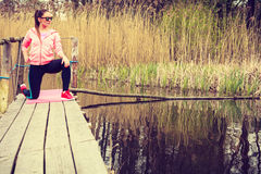 Addestramento della ragazza in vestiti sportivi sulla riva del lago Fotografia Stock
