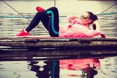Addestramento della ragazza in vestiti sportivi sulla riva del lago Fotografia Stock Libera da Diritti