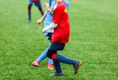 Addestramento di calcio per i bambini Ragazzi in abiti sportivi rossi blu sul campo di calcio I giovani calciatori gocciolano e d fotografie stock