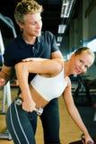 Addestramento di Dumbbell con l'addestratore Immagine Stock