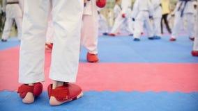 Addestramento di karatè - gruppo di adolescenti di karateka in scarpe rosse e kimono bianco archivi video
