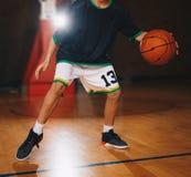 Addestramento di pallacanestro dei bambini Il giovane giocatore di pallacanestro gocciola la palla sulla corte di legno immagine stock libera da diritti