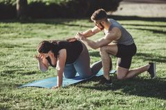 Addestramento di peso eccessivo della donna con il supporto dell'istruttore Fotografia Stock Libera da Diritti