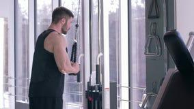 Addestramento di potere, forte sportivo che fa allenamento della costruzione del muscolo sul simulatore della trazione mentre lav video d archivio