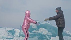 Addestramento di sport di amore La giovane coppia si diverte durante la passeggiata dell'inverno contro fondo di ghiaccio del lag stock footage