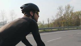 Addestramento di Triathlete sulla bicicletta Il lato indietro segue il colpo Triathlete attivo allegro che guida una bicicletta C stock footage