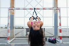 Addestramento divertente allegro della donna con le cinghie di forma fisica del trx Fotografia Stock
