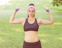 Addestramento esile della donna di forma fisica con le teste di legno Fotografia Stock