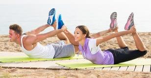 Addestramento felice della donna e dell'uomo sulla spiaggia dal mare Immagine Stock