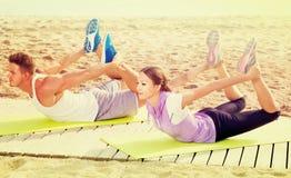 Addestramento felice della donna e dell'uomo sulla spiaggia dal mare Fotografia Stock
