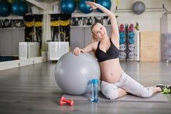 Addestramento felice della donna incinta alla palestra con la palla dei pilates Immagine Stock