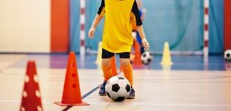 Addestramento futsal di calcio per i bambini Esercitazione di gocciolamento del cono di addestramento di calcio fotografie stock libere da diritti