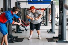 Addestramento grasso con l'istruttore, allenamento duro della donna Immagine Stock