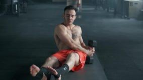 Addestramento muscolare dell'uomo nella palestra Allenamento dell'ABS con la testa di legno archivi video