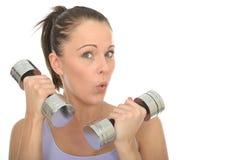 Addestramento sano della giovane donna di misura con i pesi muti di Bell che tirano espressione facciale sciocca Immagine Stock Libera da Diritti
