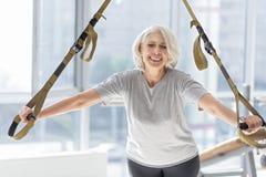 Addestramento sorridente estatico della donna con l'attrezzatura di sport speciale Immagini Stock Libere da Diritti