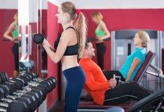Addestramento sorridente felice positivo di sollevamento pesi della gente nella salute c Fotografia Stock