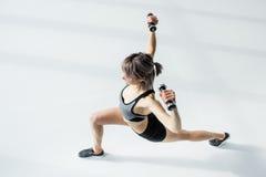 Addestramento sportivo della donna con le teste di legno su bianco Fotografie Stock Libere da Diritti
