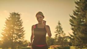 Addestramento sportivo della donna funzionato pulendo sudore dalla fronte nel parco di estate alla sera archivi video