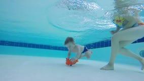 Addestramento in uno stagno, nuoto del figlio e della madre del bambino subacqueo video d archivio