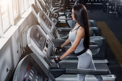 Addestrando in ginnastica Calorie dell'ustione della ragazza di forma fisica sulla pedana mobile Immagini Stock