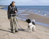 Addestratore di cani alla spiaggia Fotografia Stock