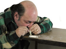 The Addict. A male drug addict snorting white powder from a table top Royalty Free Stock Photography