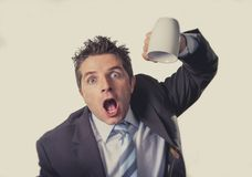 Addict businessman holding empty cup of coffee in caffeine addiction concept. Young addict business man in suit and tie holding empty cup of coffee anxious Royalty Free Stock Photography