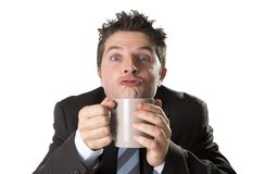 Addict businessman in suit and tie holding cup of coffee as maniac in caffeine addiction Royalty Free Stock Image