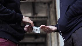 Addict buying dose from drug dealer on street 4. Drug trafficking, crime, addiction and sale concept - addict buying dose from drug dealer on street stock footage