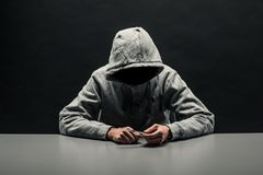 Addict in gray hoodie on the head suffers from addiction on a da stock photo