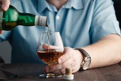 Addict issue, man pours himself a whiskey Stock Photography