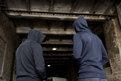 Addict men or criminals in hoodies on street Royalty Free Stock Photo