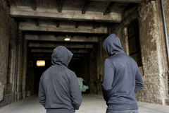 Addict men or criminals in hoodies on street Royalty Free Stock Photos