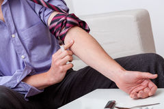 Addict preparing arm for injection Royalty Free Stock Photo