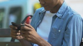 Addicted Afro-American male teenager nervously playing video game on smartphone. Stock footage stock video