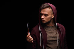 An addicted junkie in a purple sweatshirt suffers from drug addiction with a syringe in a hand on a black background. A drug user with a syringe with an stock images