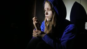 Addicted junkie teen girl with a syringe sitting on a floor and thinking about something. 4K UHD. stock video footage