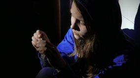 Addicted junkie teen girl with a syringe sitting on a floor and thinking about something. 4K UHD. stock footage
