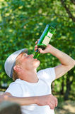 Addicted middle-aged man drinking white wine Stock Photos