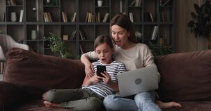 Mother using laptop daughter holding smartphone seated on couch