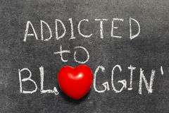 Addicted to blogging. Phrase handwritten on blackboard with heart symbol instead of O royalty free stock photos