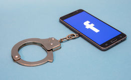 Facebook addicted. Handcuffs and telephone isolated on blue background. Part of project Addicted Royalty Free Stock Images