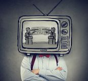 Addicted to fake news man with television instead of his head watching TV. With two politicians, liar businessmen having a debate royalty free stock photos