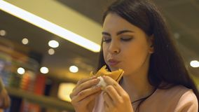 Addicted to fast food lady eating hamburger in restaurant, hungry student snack