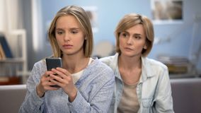 Addicted to smartphone daughter avoiding family talk with mother, naughty child. Stock photo stock photo